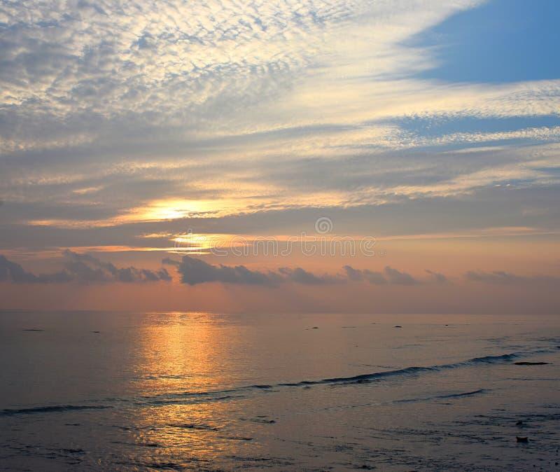 Sol levante dietro le nuvole all'orizzonte con il cielo luminoso di mattina con il modello bianco della nuvola a Serene Beach fotografia stock