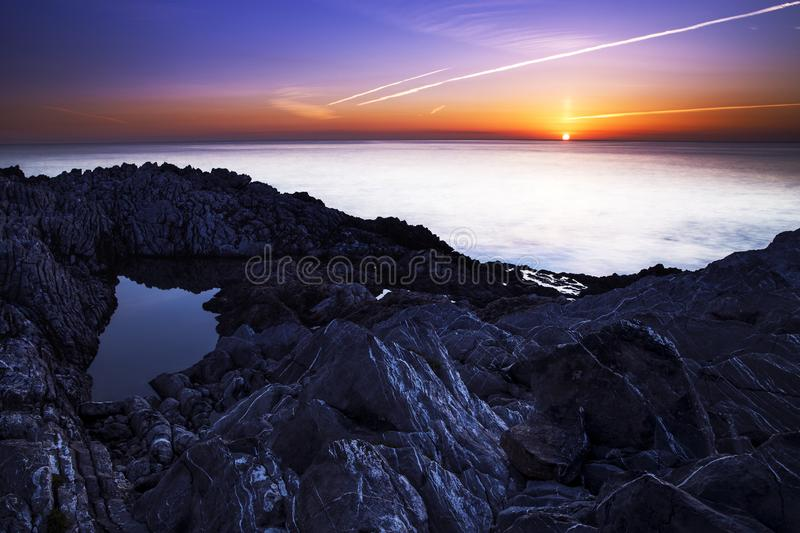 The sun rises in front of the rock pond royalty free stock photo