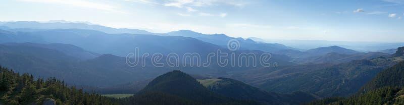 Sol nebuloso sobre los picos de montañas fotos de archivo