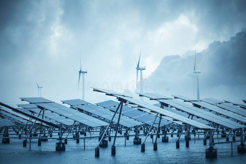 Sol- och vindkraft i kust- gyttjalägenhet royaltyfri bild