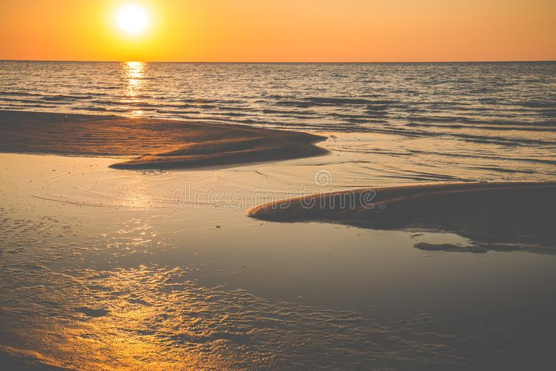 sol, ondas y arena anaranjados imagen de archivo