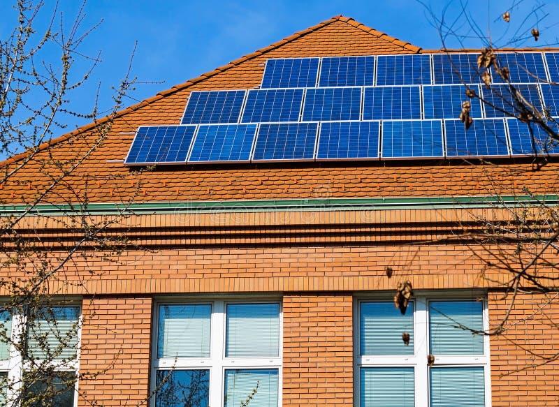 Sol- paneler p? taket av en byggnad royaltyfri foto