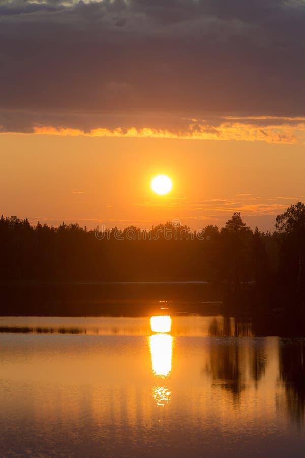 Sol poniente sobre un lago del bosque fotografía de archivo libre de regalías