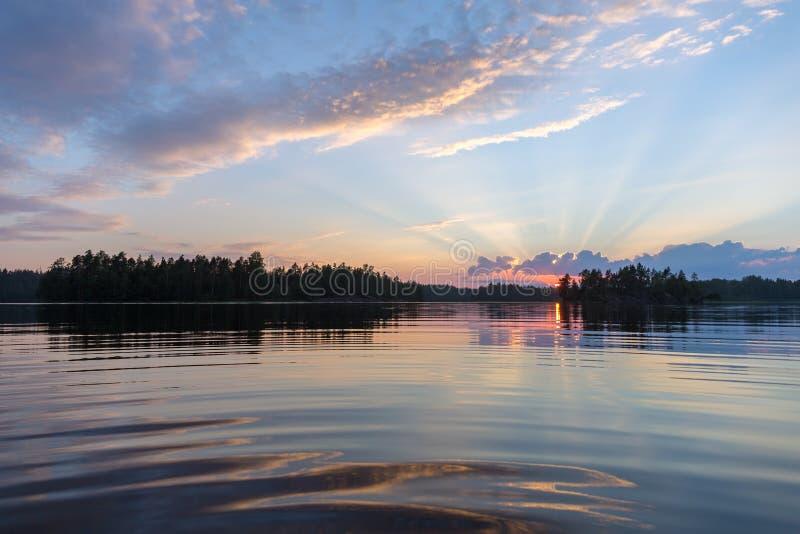Sol poniente sobre un lago del bosque fotografía de archivo