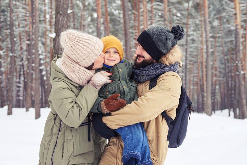 Sol positivo rodeado por los padres cariñosos durante el paseo del invierno foto de archivo libre de regalías