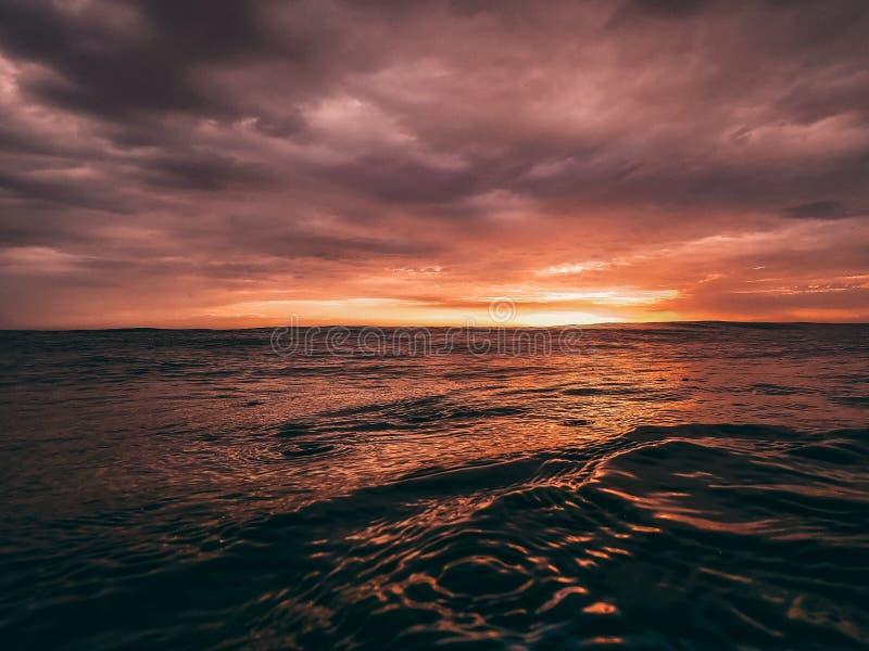 Sol rojo sobre el océano fotos de archivo