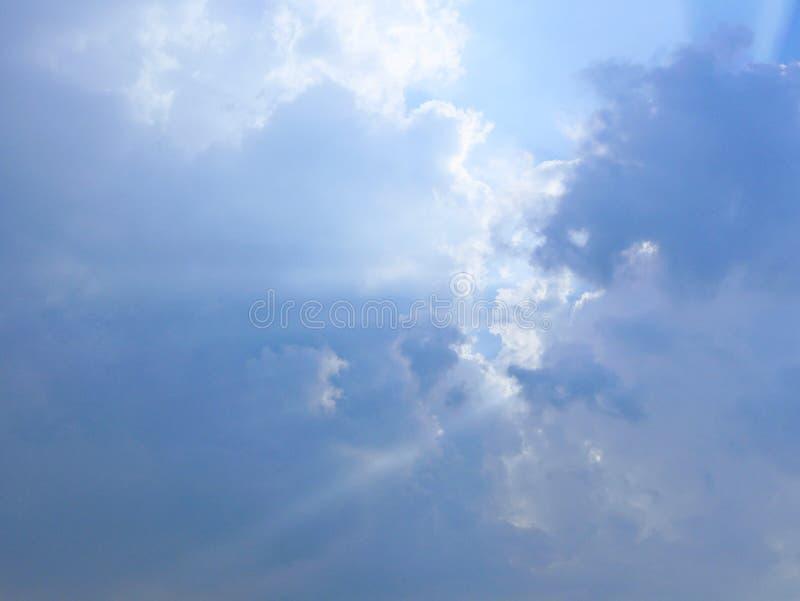 Sol` s rays bristning till och med molnen i den blåa himlen arkivfoto