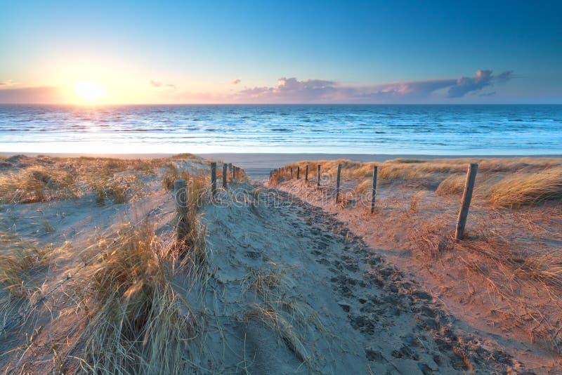 Sol sobre la trayectoria de la arena a la costa de Mar del Norte foto de archivo