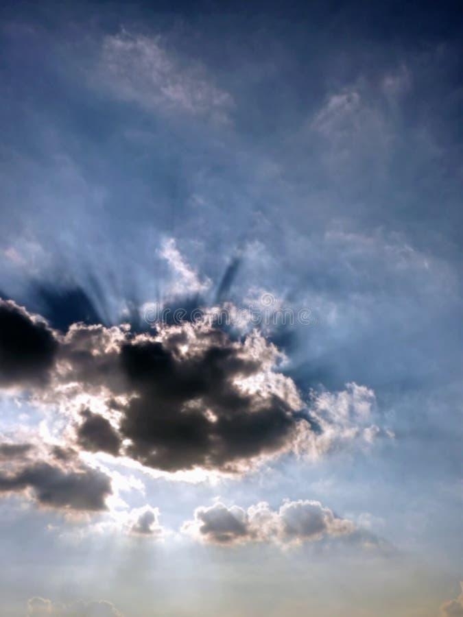 Sol som bakifrån skiner moln royaltyfri foto