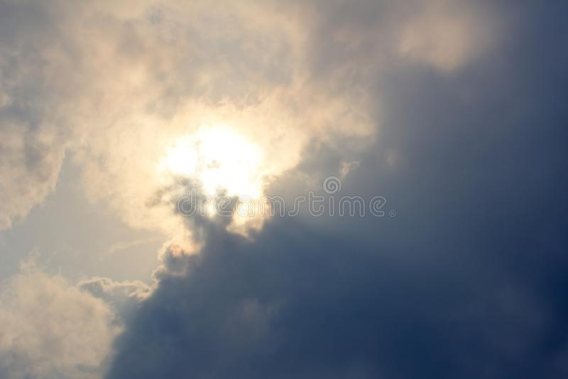 Sol som bakifrån stiger mörka moln arkivfoto