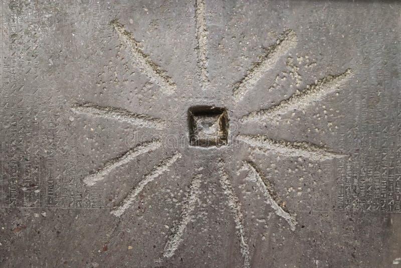 Sol-som design på forntida egyptisk byggnad med svaga hieroglyf till sidorna arkivbilder