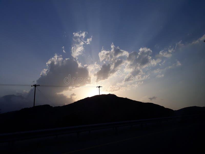 Sol som försöker att fördela dess ljus, medan moln försöker att täcka det De solstrålar ser härliga royaltyfri bild