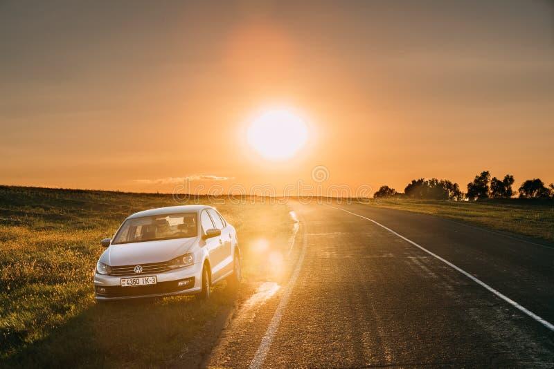 Sol som nära stiger över VW Volkswagen Polo Vento Sedan Car Parking royaltyfri fotografi