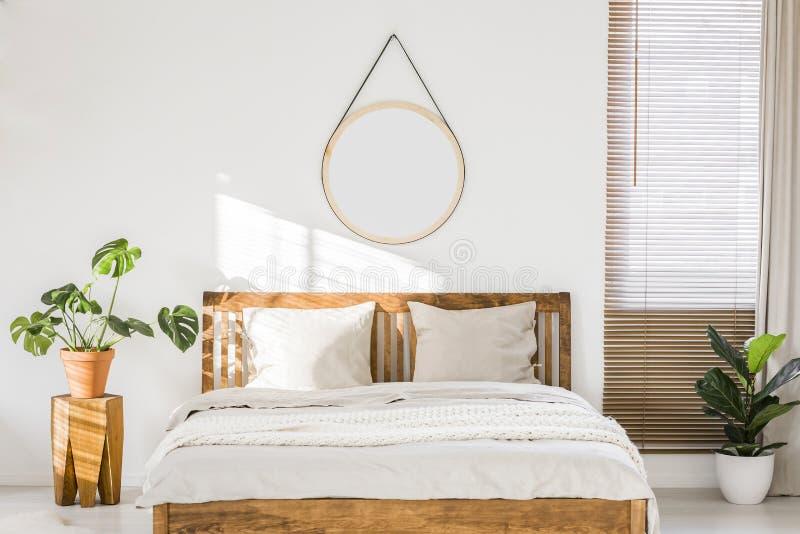 Sol som skiner på en vit vägg med en rund spegel i en minimalist royaltyfri bild