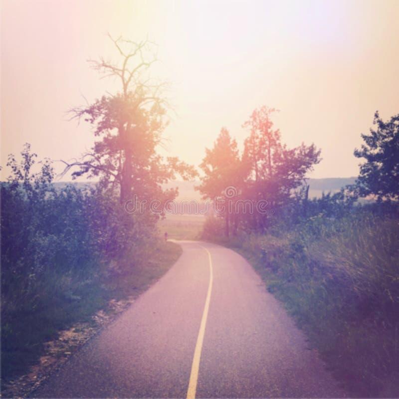 Sol som ställer in över den tomma landsvägen arkivfoto