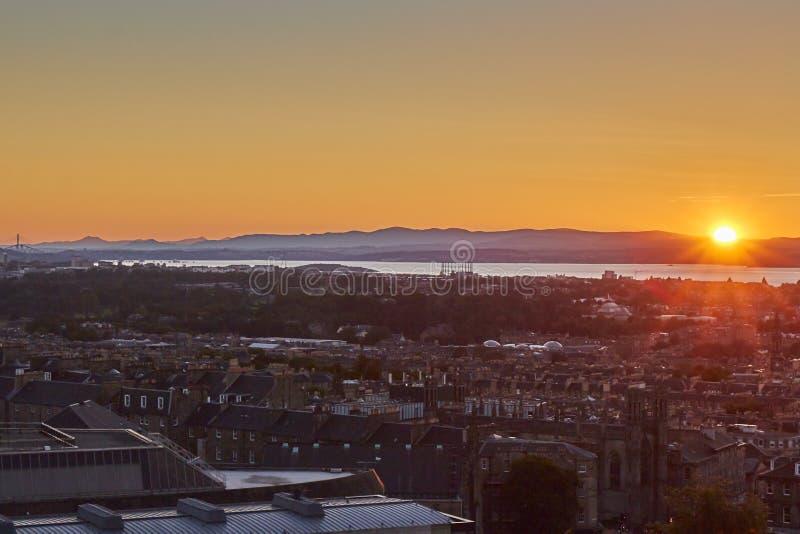 Sol som ställer in över horisont med Edinburgcityscape i förgrunden, Skottland, Förenade kungariket royaltyfria foton