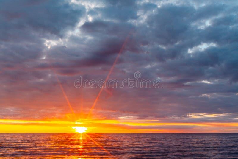 Sol som ställer in över lugna havvatten royaltyfri fotografi
