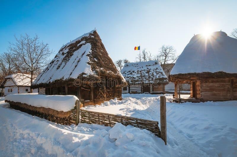 Sol som värmer en traditionell rumänsk hemman som upp täckas i snö arkivfoto
