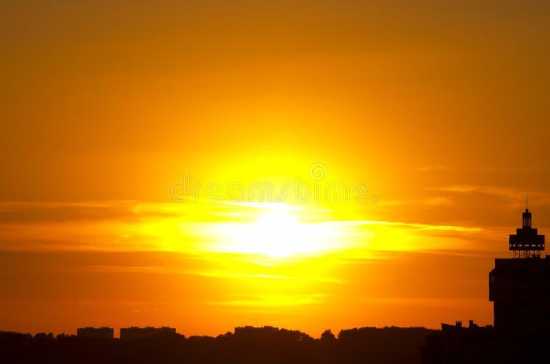 Sol- tryckvåg för röd solnedgång, sol på moln, stadskontur royaltyfria bilder