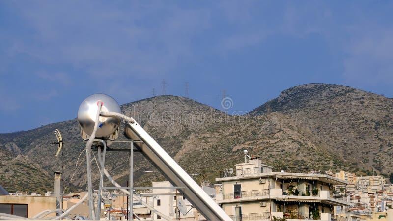 Sol- varmvattensystem och förorts- Atenhus, Grekland royaltyfri foto