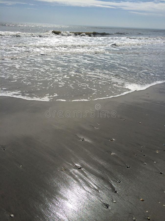 Sol, vatten och sand royaltyfria foton