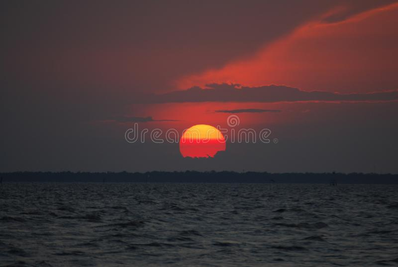 Sol vermelho e por do sol vermelho do céu sobre o oceano imagem de stock