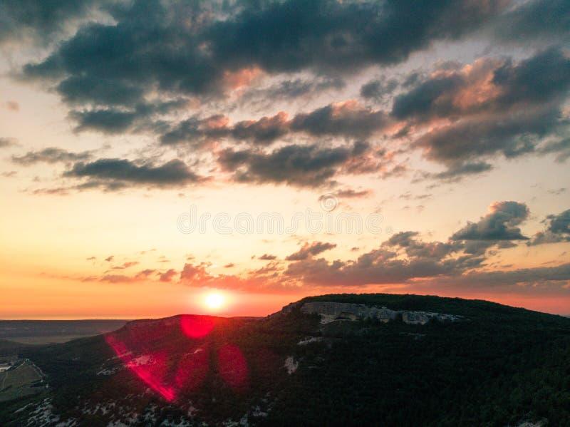 Sol vermelho sobre o alargamento da montanha e da lente fotos de stock royalty free