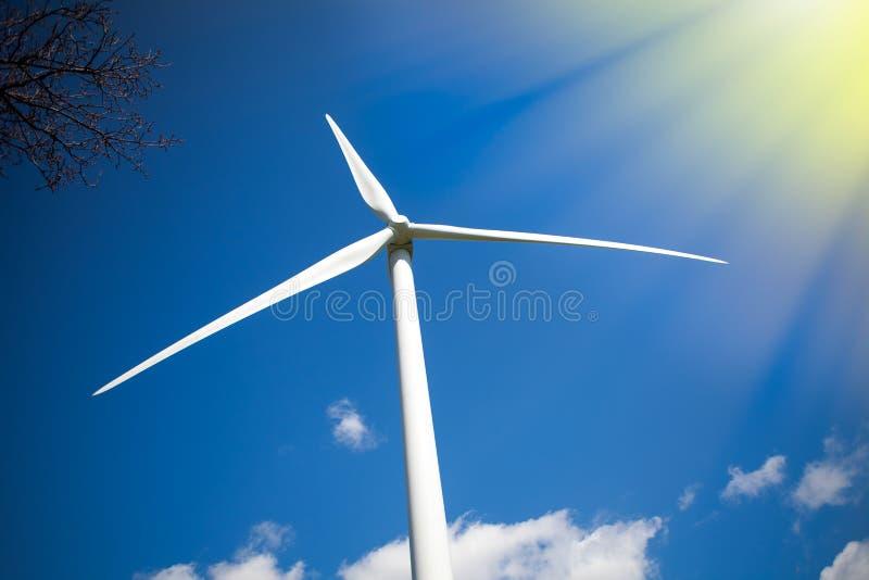 sol- wind för ström Turbin i solsken mot blå himmel arkivbilder