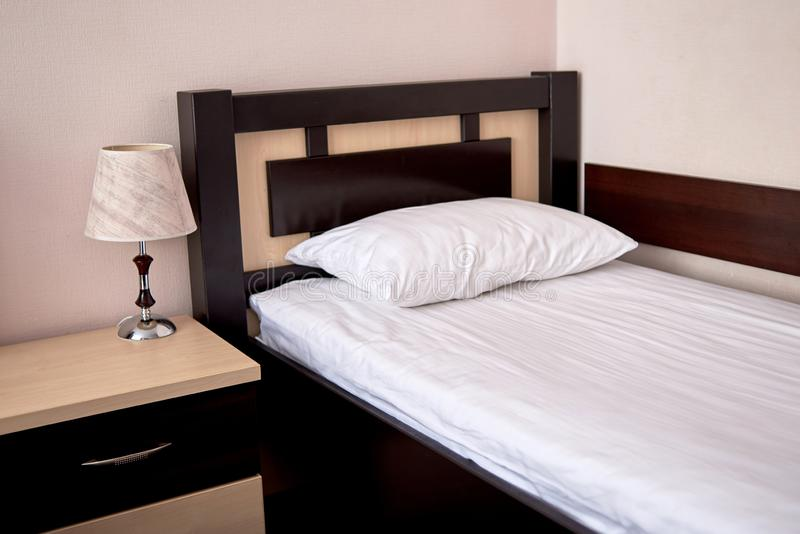 Sola cama vacía con el cabecero de madera marrón y la almohada suave blanca en el interior del dormitorio del hotel, espacio de l foto de archivo libre de regalías
