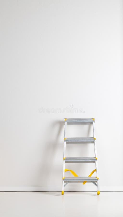 Sola escalera de paso plegable de aluminio del metal que se inclina contra la pared blanca del yeso imagen de archivo libre de regalías