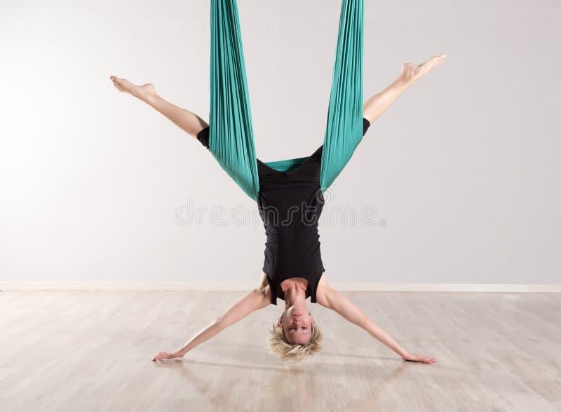 Sola mujer al revés que hace fracturas aéreas de la yoga fotos de archivo libres de regalías