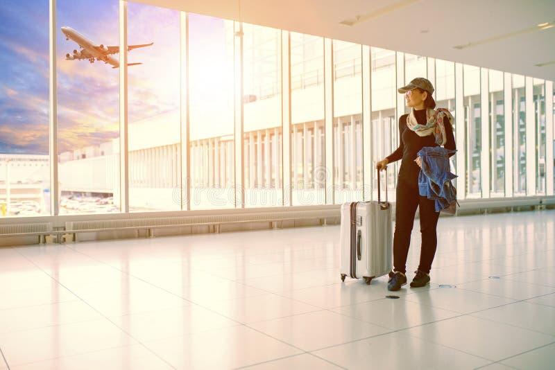 Sola mujer y equipaje que viaja que se colocan en terminal de aeropuerto fotos de archivo libres de regalías