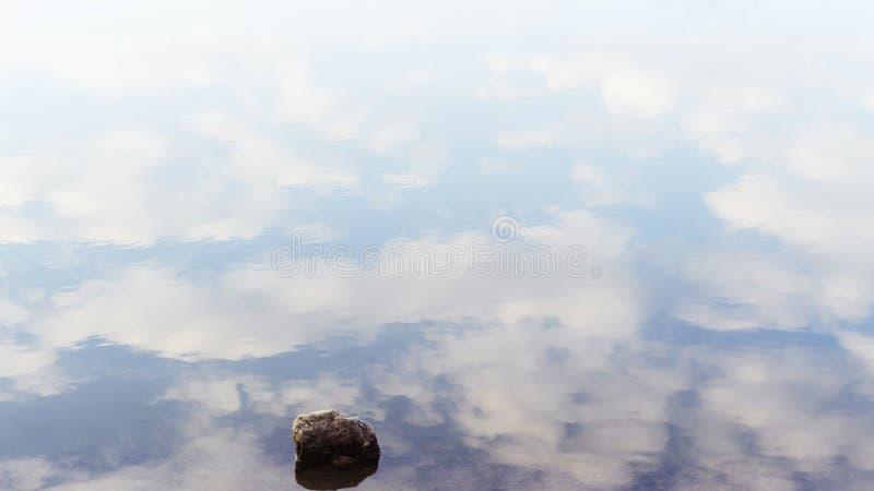 Sola piedra en agua tranquila con las nubes reflectoras fotos de archivo