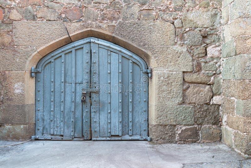 Sola puerta de madera antigua del castillo en pared vieja de la ciudad Puerta de madera medieval arqueada en una pared de piedra fotos de archivo libres de regalías
