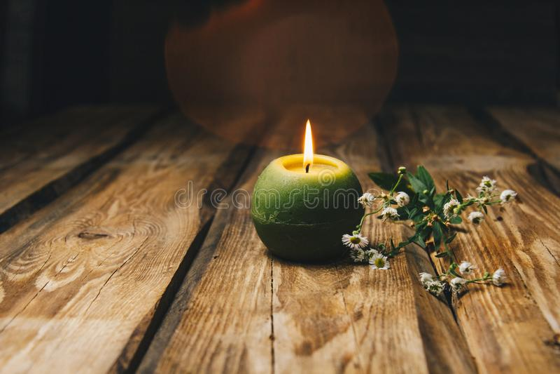 Sola vela bola-formada verde con una flor seca que quema en un primer de madera rústico de la tabla imagenes de archivo