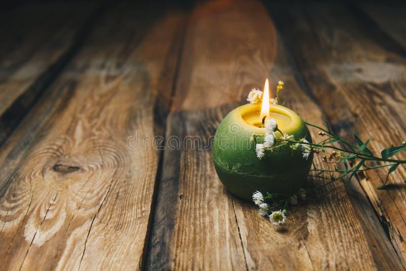 Sola vela bola-formada verde con una flor seca que quema en un primer de madera rústico de la tabla imagen de archivo