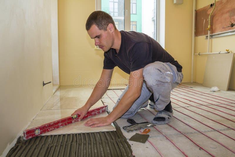Solador del trabajador joven que instala las baldosas cerámicas usando palanca en piso del cemento con el sistema rojo del alambr imagenes de archivo