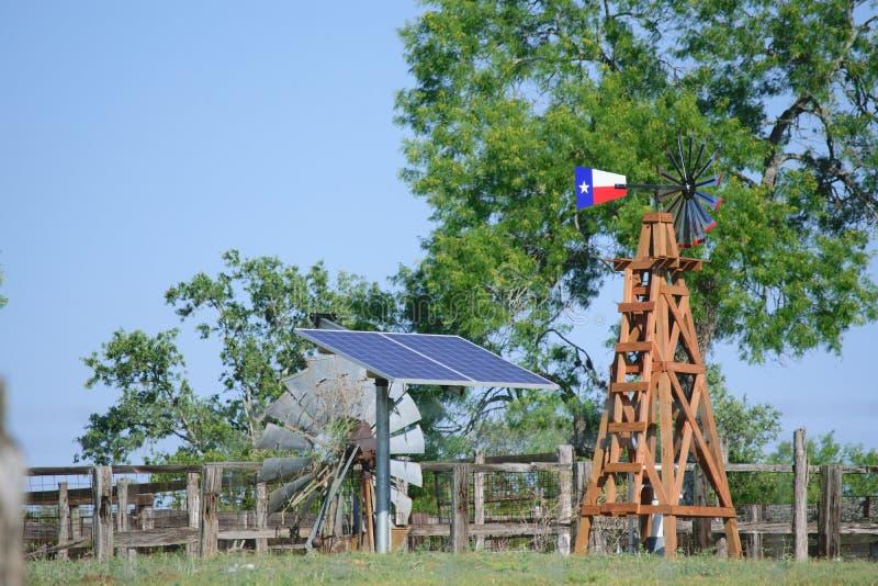 Solaire puits d'eau avec Texas Windmill devant les arbres de vert d'été, la barrière de ranch de ferme et le fond de ciel bleu images libres de droits