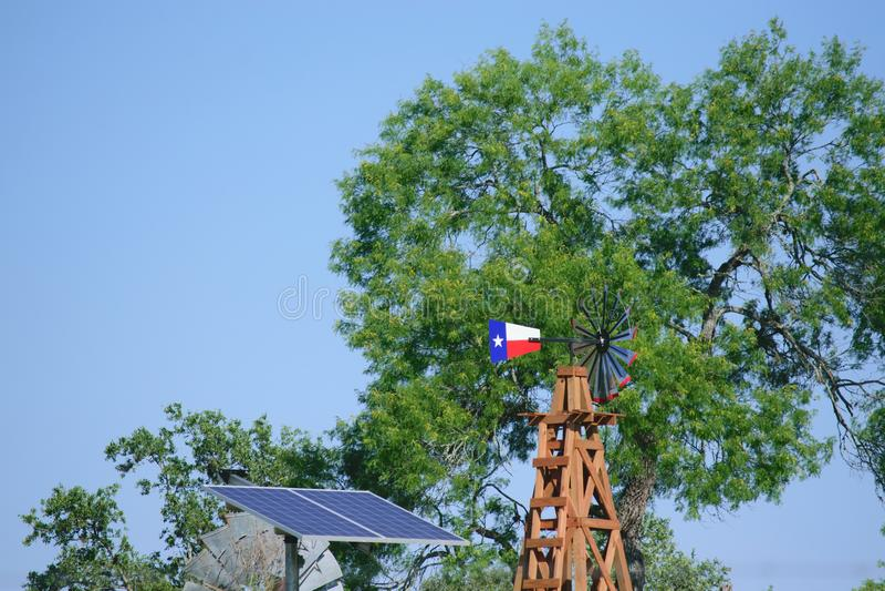 Solaire puits d'eau avec Texas Windmill devant les arbres de vert d'été, la barrière de ranch de ferme et le fond de ciel bleu images stock