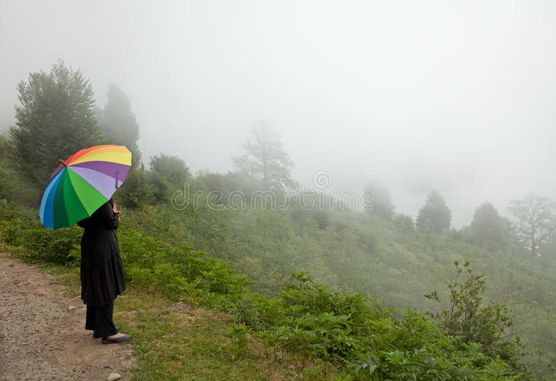 Solamente en la niebla con el paraguas colorido fotos de archivo
