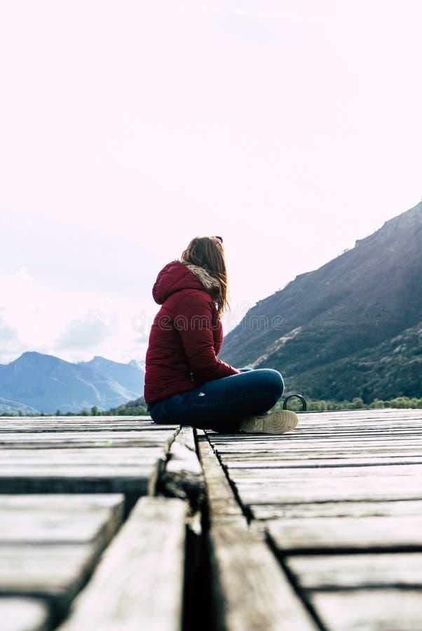 Solamente las mujeres se relajan en muelle de madera en el lago pacífico Meditación de la muchacha con la chaqueta roja en un emb imagen de archivo libre de regalías