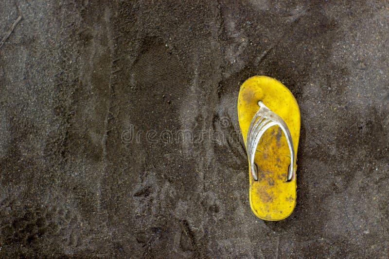 Solamente una sandalia amarilla sucia en la arena negra imagen de archivo