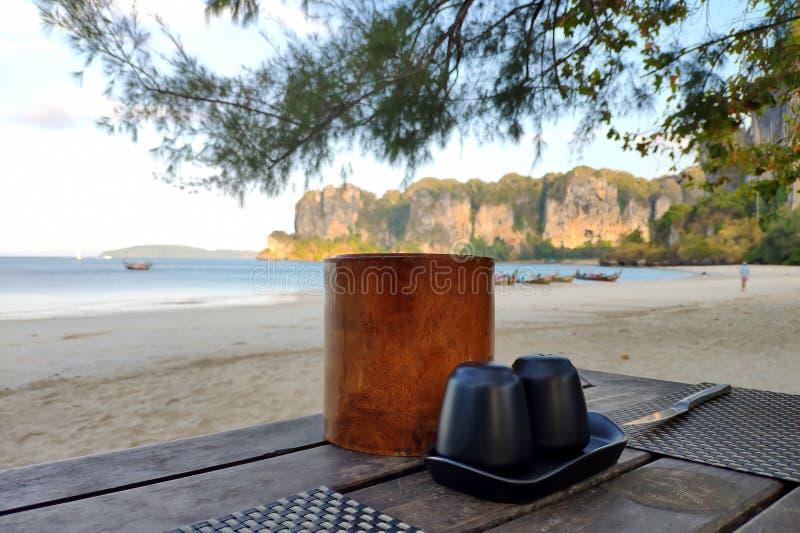 Solankowy potrząsacz, pieprzowy potrząsacz i pieluchy na drewnianym stole na piaskowatym brzeg tropikalna wyspa blisko morza, obraz stock