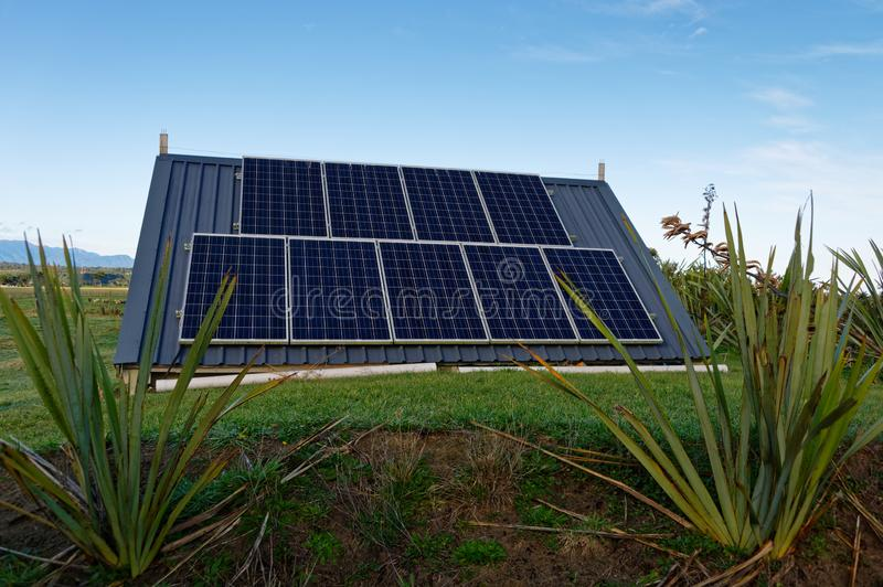 A solar array of panels for an off grid system. An off grid solar power system shown in situ, allowing self sufficient electricity generation stock photography