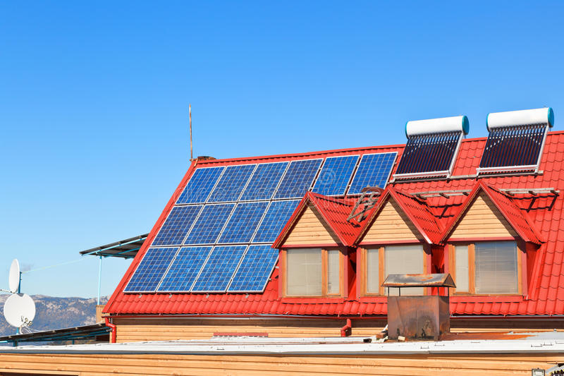 Solar Batteries and heaters on house roof. Modern energy-saving technology - Solar Batteries and heaters on house roof royalty free stock photography