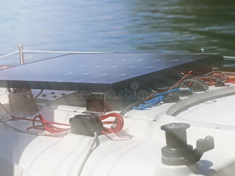 Solar battery for the development of electric current under the influence of sunlight mounted on the deck of a small sailing yacht. Electrification of the royalty free stock photography