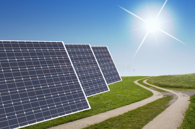 Solar cell concept. Solar cells with a path in the green in back a blue sky with sun stock photography