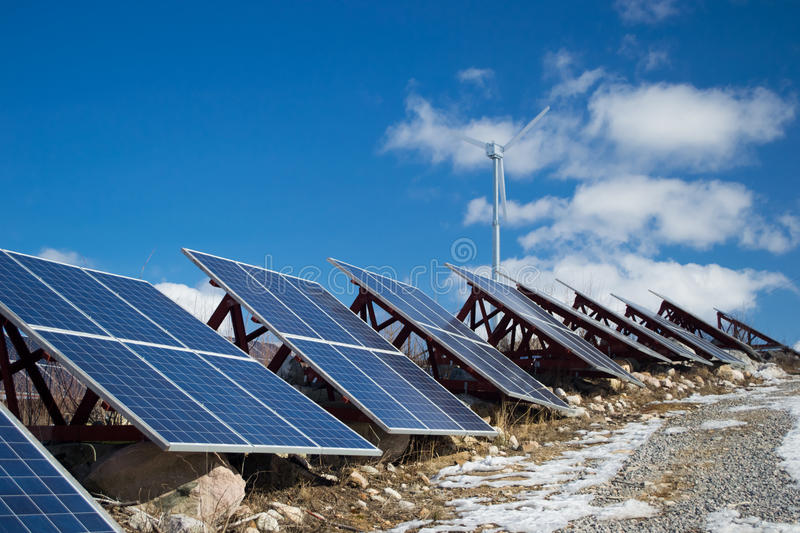 Solar energy. Solar cell panels with wind turbine in the background. Renewable energy sources stock images