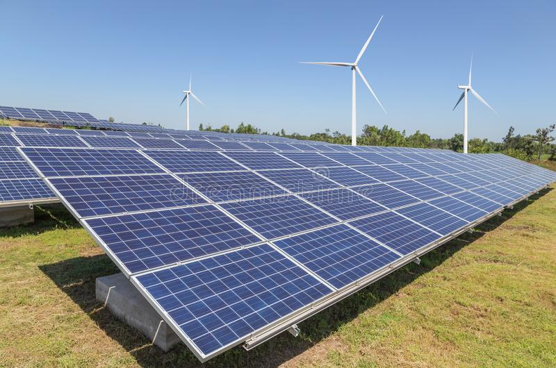 Solar cells with wind turbines generating electricity in hybrid power plant systems station royalty free stock photography