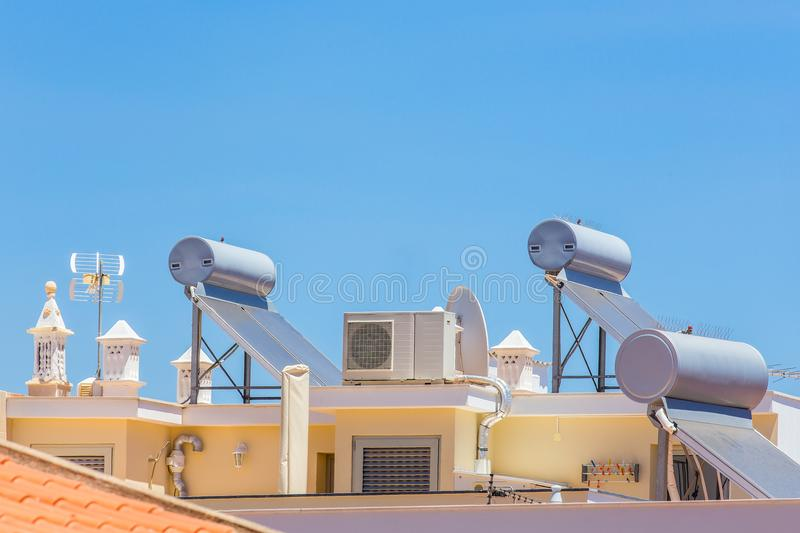 Solar panels and boilers on roof of building. Solar collectors and boilers with airco on roof of house stock images